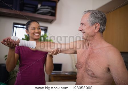 Smiling female therapist looking at senior male patient with bandage on wrist in hospital ward