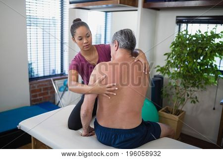Young female therapist examining back of shirtless senior male patient sitting on bed at hospital ward