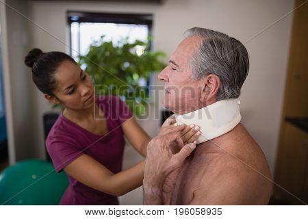 Female therapist examining neck collar on senior male patient at hospital ward