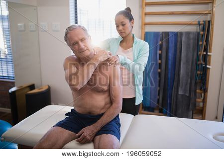 Shirtless senior male patient sitting on bed receiving neck massage from female therapist at hospital ward