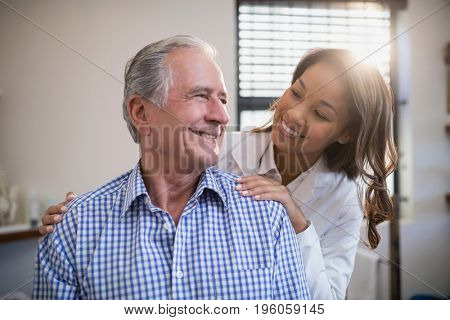 Smiling therapist and male patient looking at each other in hospital ward
