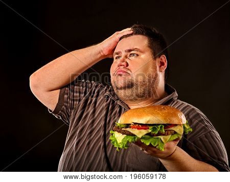 Man eating fast food hamberger. Fat person made great huge hamburger and admires him, intending to eat it. Junk meal leads to obesity. He is tormented by his conscience about the failure of the diet.
