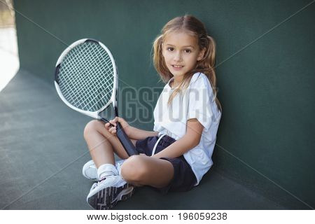 Portrait of girl holding tennis racket while sitting at court