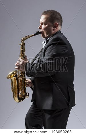 Music Concepts. Portrait of Caucasian Mature Concentrated Saxophone Player Playing the Instrument Against White Background. Vertical Image