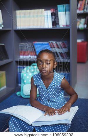 Girl reading braille against bookshelf in library