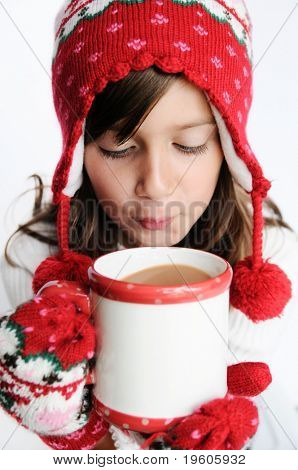 A cute young girl drinking hot cocoa