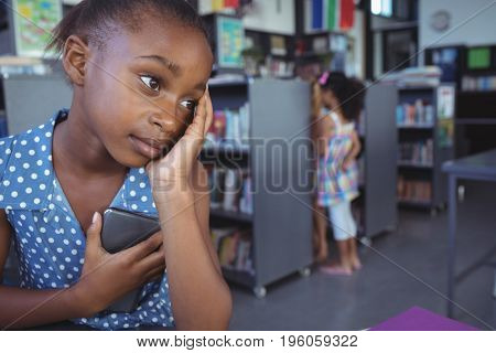 Close up of thoughtful girl looking away while holding mobile phone in library