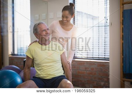 Smiling female therapist looking at senior male patient against window at hosital