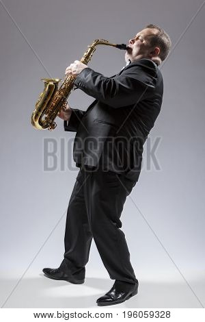 Music Concepts. Full Length Portrait of Caucasian Mature Concentrated Saxophone Player Playing the Instrument Against White Background. Vertical Image