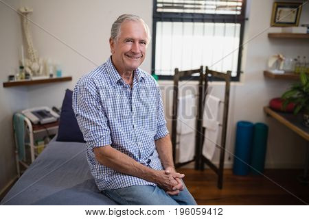 Portrait of smiling senior male patient sitting on bed against window at hospital ward