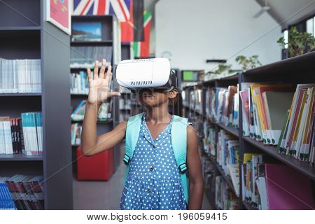 Girl gesturing while wearing virtual reality simulator in library