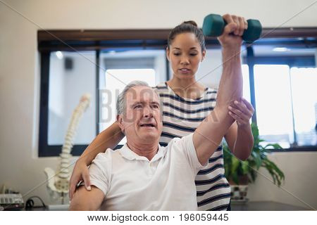 Female doctor looking at senior patient lifting dumbbell in hospital ward
