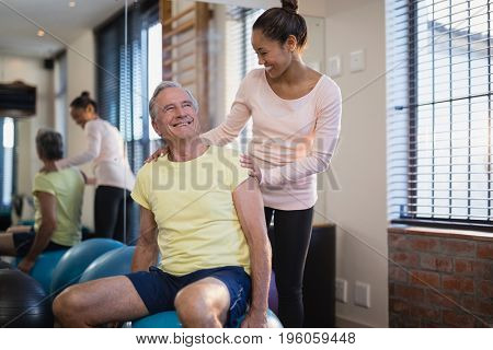 Smiling senior male patient looking at female therapist against window at hosital