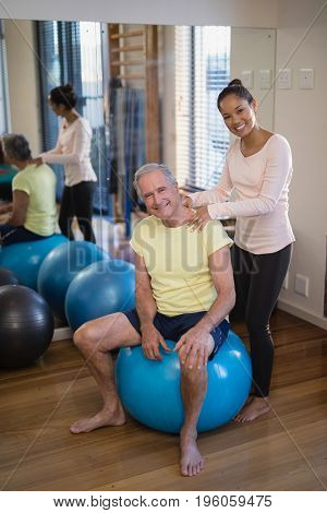 Portrait of smiling female therapist giving neck massage to senior patient sitting on exercise ball against mirror at hospital ward