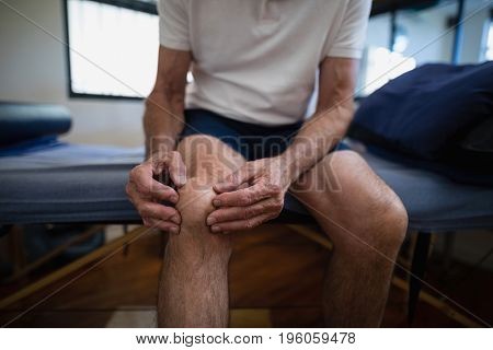 Midsection of senior male patient holding knee in pain at hospital ward