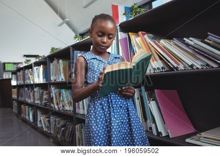 Girl reading book while standing by bookshelf in library