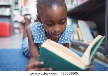 Close up of girl reading book while lying by shelf in library