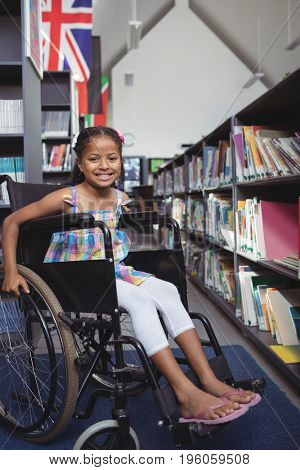 Portrait of smiling girl sitting on wheelchair by shelves in library