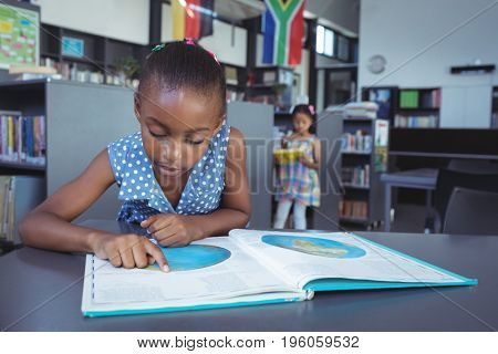 Girl reading book at desk in library