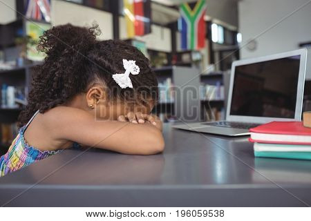Close up of sad girl leaning on table in library
