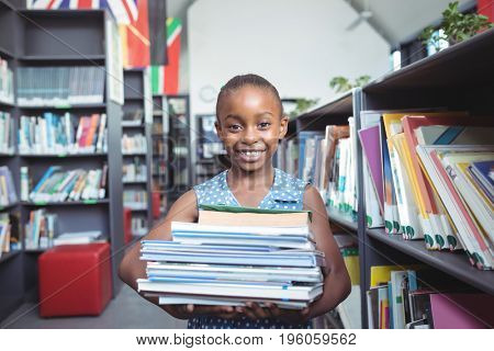 Portrait of smiling girl carrying books by shelf in library
