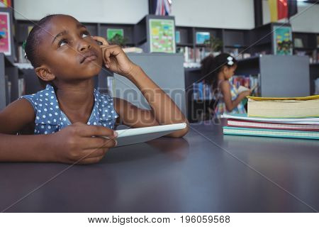 Thoughtful girl looking up while holding digital tablet at desk in library