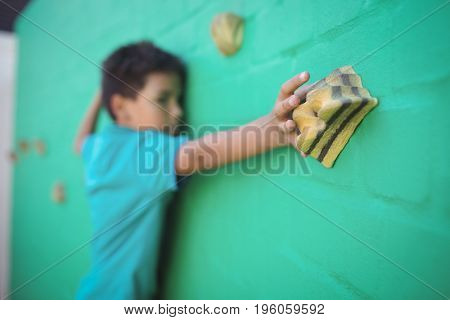 Boy reaching climbing holds on green wall