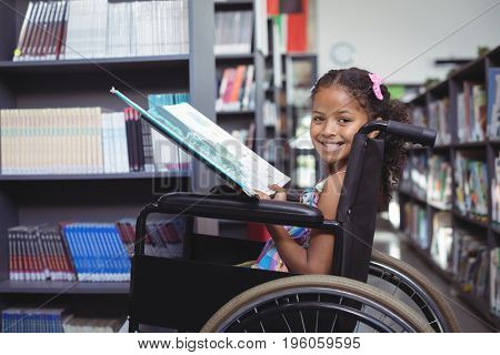 Portrait of smiling girl with book sitting on wheelchair at library