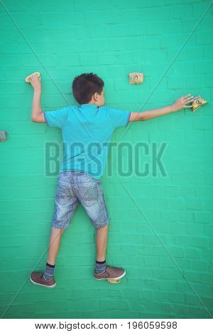 Full length rear view of boy climbing on green wall