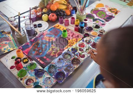 Cropped image of girl holding brush by color palettes on desk in classroom