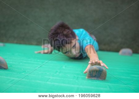 High angle view of boy reaching climbing holds on wall
