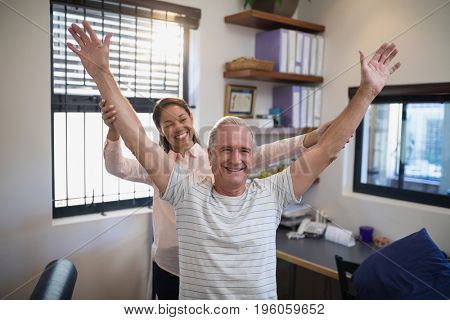 Smiling female doctor and male patient with arms raised at hospital ward