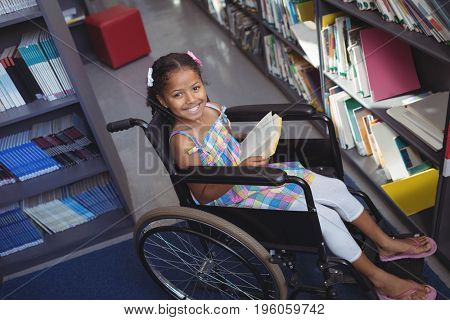 High angle portrait of smiling girl with book on wheelchair in library