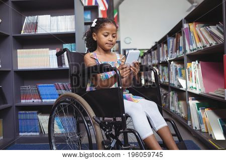Girl using digital tablet while sitting on wheelchair in library