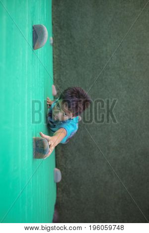 High angle view of boy reaching climbing holds on green wall