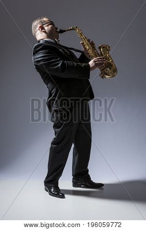 Music Concepts. Full Length Portrait of Mature Expressive Caucasian Saxophone Player in Sunglasses Playing the Saxophone in Studio Environment. Vertical Image