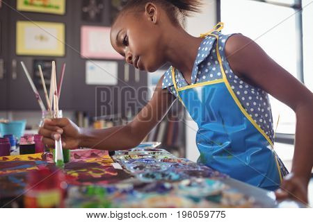 Focused elementary girl painting at desk in classroom