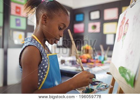 Side view of focused girl painting on canvas in classroom