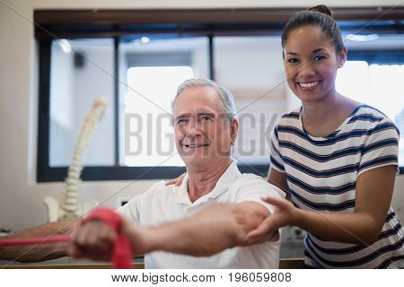 Portrait of smiling senior male patient pulling red resistance band with female doctor in hospital ward