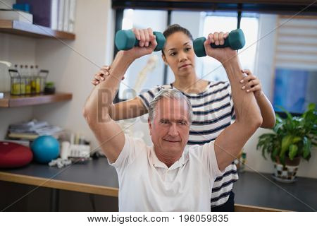 Female doctor looking at male patient lifting dumbbells in hospital ward