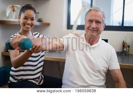 Portrait of smiling female doctor with senior male patient holding dumbbell at hospital ward