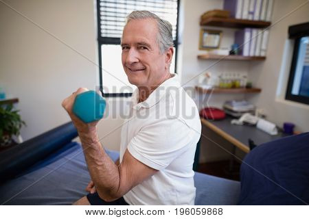 Side view portrait of smiling senior male patient lifting dumbbell at hospital ward