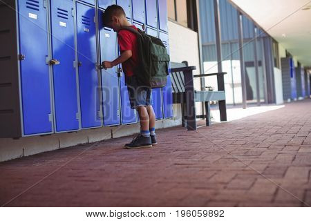 Full length of boy leaning on lockers in corridor at school