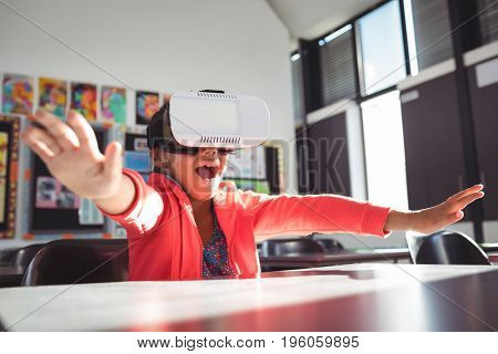 Girl with mouth open using virtual reality glasses in classroom at school