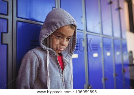 Thoughtful boy making face by lockers at school