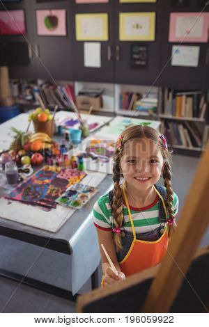 High angle portrait of girl painting on canvas in classroom