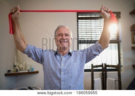 Portrait of smiling senior male patient holding red resistance band at hospital ward