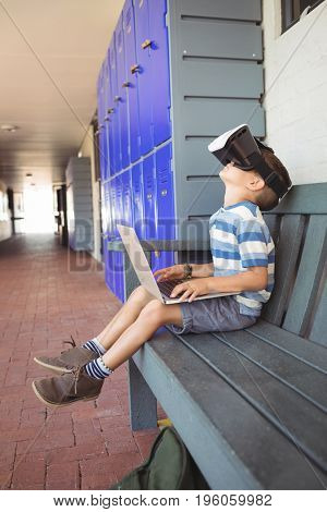 Side view of boy using laptop and virtual reality glasses while sitting on bench by lockers at school