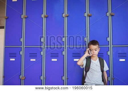 Boy talking on mobile phone while standing against lockers at school