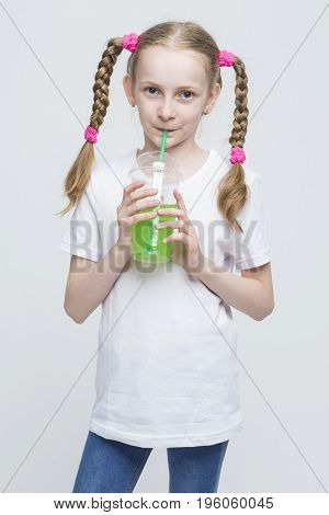 Kids Lifestyle Concepts. Portrait of Pretty Smiling Caucasian Blond Girl With Long Pigtails Holding Cup and Drinking Green Juice Through Straw. Vertical Image
